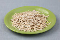Rolled oats on a green plate Royalty Free Stock Images