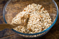 Rolled oats, nuts and spices in bowl on wooden table Stock Image