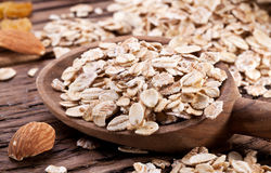 Rolled oats and nuts. Rolled oats in the wooden spoon over old wooden table royalty free stock images