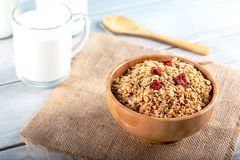 Rolled oats or oat flakes in bowl with wooden spoonsand bottle of milk. On background stock image