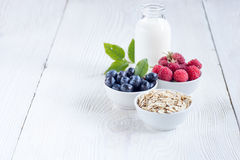 Rolled oats (oat flakes) with milk, raspberries and blueberries. Cereal and various delicious ingredients for breakfast and white wooden background Royalty Free Stock Photo