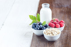 Rolled oats (oat flakes) with milk, raspberries and blueberries. Cereal and various delicious ingredients for breakfast and white wooden background Royalty Free Stock Photography
