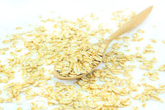 Rolled oats (oat flakes) in a wooden spoon on a rolled oats and white background Stock Photos