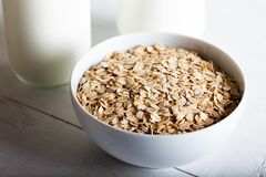 Free Rolled Oats Or Oat Flakes In Bowl With Bottle Of Milk On White Wooden Table Stock Photo - 160748050