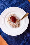 Rolled oats porridge with milk and jelly Stock Images
