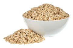 Rolled oats. In a white ceramic plate over white background Stock Photo