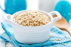 Rolled oats on white wooden background Royalty Free Stock Images