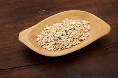 Rolled oats in wooden bowl Stock Images