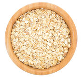 Rolled oats in wooden bowl isolated. Royalty Free Stock Photo
