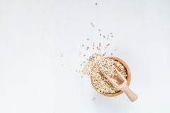 Rolled oats in wooden bowl on white. Rolled oats in bowl on white table, top view. Copy space Royalty Free Stock Photos