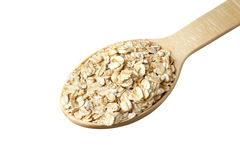 Rolled oats in a wooden spoon. Isolated on white Royalty Free Stock Photos