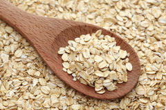 Rolled oats in a wooden spoon. Rolled oats (oat flakes) in a wooden spoon on a rolled oats background. Close-up Royalty Free Stock Photos