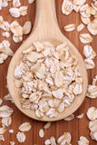 Rolled oats in a wooden spoon Stock Images