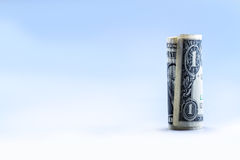 Rolled one dollar banknote stand vertical. Blue background Stock Photography