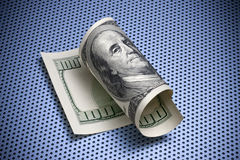 Rolled One Hundred Dollar Bill. A rolled up American one hundred dollar bill  on a blue toned metal background Royalty Free Stock Photos