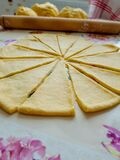 Rolled out dough cut into triangles. Behind it is a rolling pin and three balls of dough. Homemade cooking.