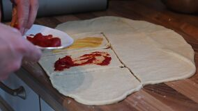 Rolled out dough on the kitchen surface is topped with individual ingredients