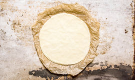 The rolled out pizza dough on the old paper. Stock Photos