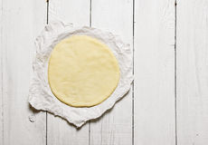 The rolled out pizza dough on the paper. stock photography