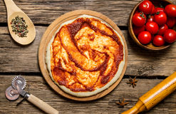 The rolled out pizza dough with tomato sauce, rolling pin and spices. Royalty Free Stock Photography