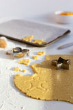 Rolled out Sweet Biscuit Dough with Festive Cookie Cutters on White Table. Festive baking scene of sweet biscuit dough rolled out on white table with christmas Royalty Free Stock Photo