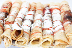 Rolled pancakes with powdered sugar and strawberry syrup Stock Images