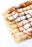 Rolled pancakes with powdered sugar and strawberry syrup Royalty Free Stock Image