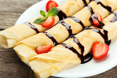 Rolled pancakes with strawberry on plate on grey wooden background. Royalty Free Stock Photo