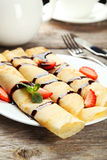 Rolled pancakes with strawberry on plate on grey wooden background Royalty Free Stock Images