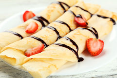 Rolled pancakes with strawberry on plate on white wooden background. Stock Images
