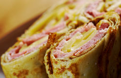 Rolled pancakes stuffed ham and cheese. Stock Images