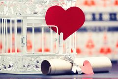 Rolled paper and red paper hearts, next to white retro bird cage. Royalty Free Stock Photo