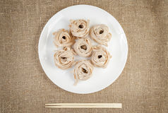 Rolled pasta on linen background with bamboo chopsticks Royalty Free Stock Photography