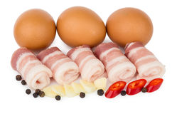 Rolled pieces of bacon, pepper, garlic and chicken eggs Stock Photo
