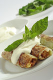 Rolled pore's leaves with cream and basil. Close up view on rolled and fried pore's leaves stuffed with buckwheat groats passed with cream (creme fraiche) and stock image