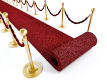 Rolled red carpet and velvet ropes Stock Images