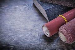 Rolled sandpaper sanding sponges on vintage wooden board abrasiv Royalty Free Stock Photos