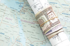 Rolled saudi arabian money in a blueprint Royalty Free Stock Images