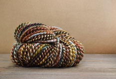 Rolled skein of hand spun variegated yarn made from sheep's wool against a brown paper background Royalty Free Stock Images