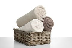 Rolled soft terry towels in wicker basket. On white background stock image