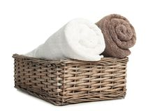 Rolled soft terry towels in wicker basket. On white background stock photography