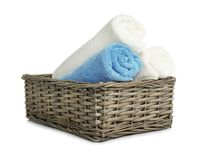 Rolled soft terry towels in wicker basket. On white background stock photos