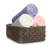 Rolled soft terry towels in wicker basket on white. Background stock images
