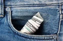 Rolled straw hundred-dollar bills in your pocket. Old blue jeans Royalty Free Stock Photography