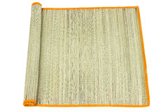 Rolled straw mat on white Stock Photography