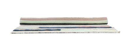 Rolled striped carpet on white background. Interior element royalty free stock photos