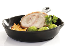 Rolled Suckling Pig Roast with potatoes and Brussels sprouts in frying pan Royalty Free Stock Photography