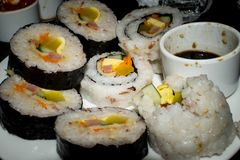 Rolled sushi arranged on circled shape plate with a soy sauce. Asian Cuisine stock photography