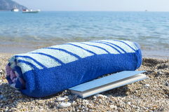 Rolled towel and a book on the beach Royalty Free Stock Image