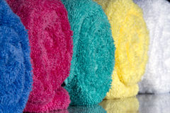 Rolled Towels. Close up shot of a group of colored, rolled towels with reflections in a studio setting royalty free stock images
